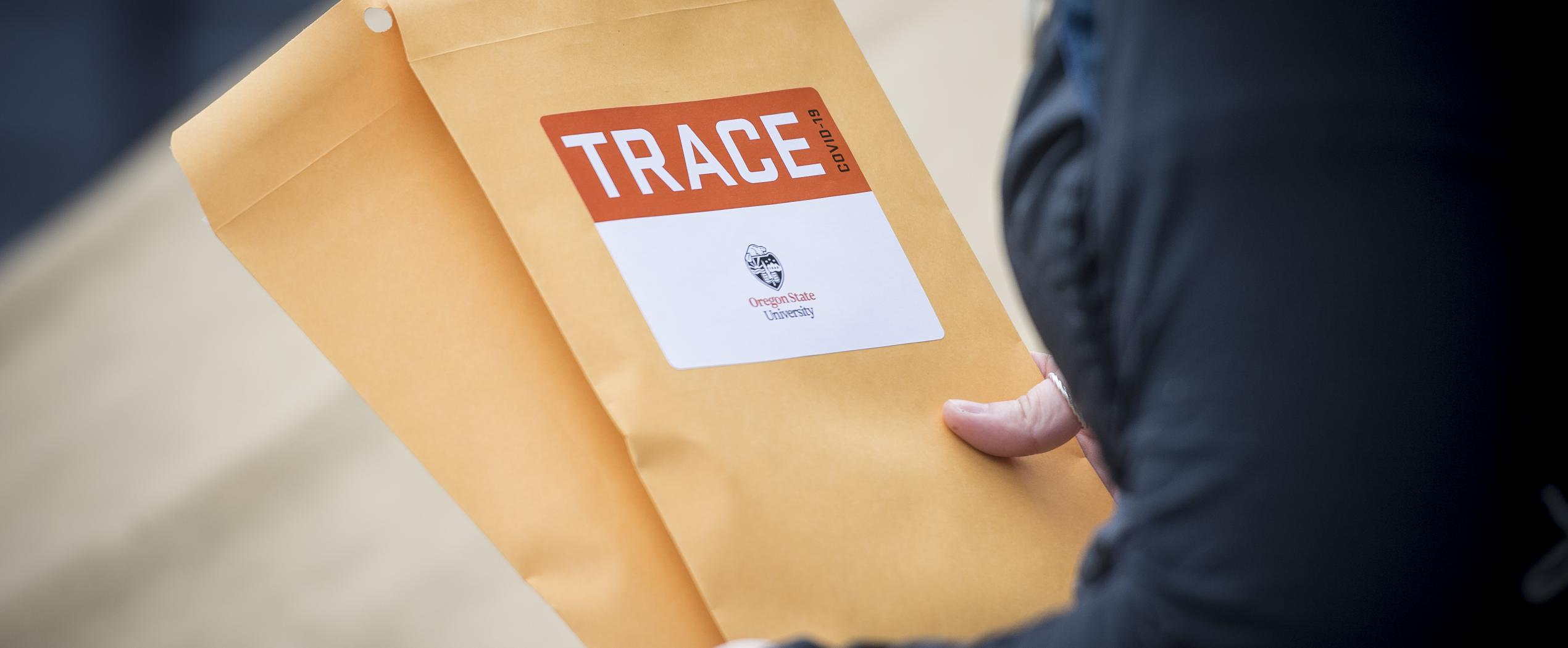 A TRACE volunteer holds envelopes