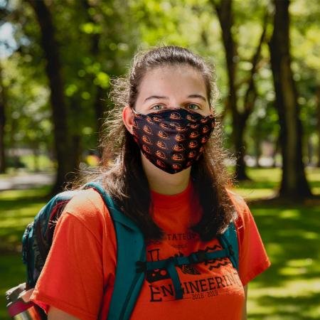 OSU student wearing face mask in a field on OSU Corvallis campus.