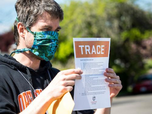 A TRACE volunteer in a face mask holds up a TRACE information sheet